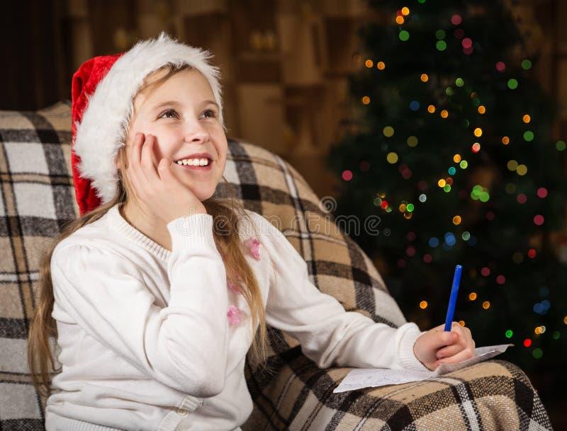 La muchacha alegre escribe una letra a Santa Claus fotos de archivo libres de regalías