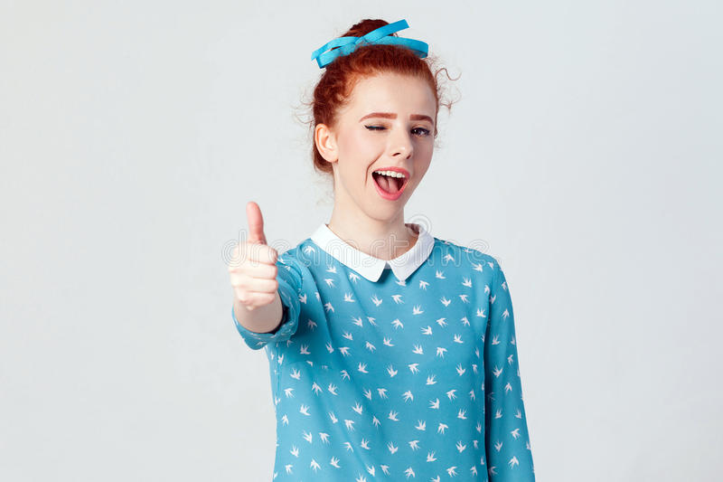 La muchacha alegre hermosa joven del pelirrojo que muestra el pulgar para arriba y sonrisa y guiño dentudos en la cámara imagenes de archivo