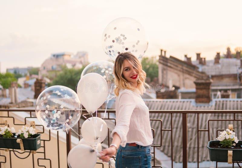 La muchacha alegre joven sostiene muchos globos en balcón o el tejado fotos de archivo