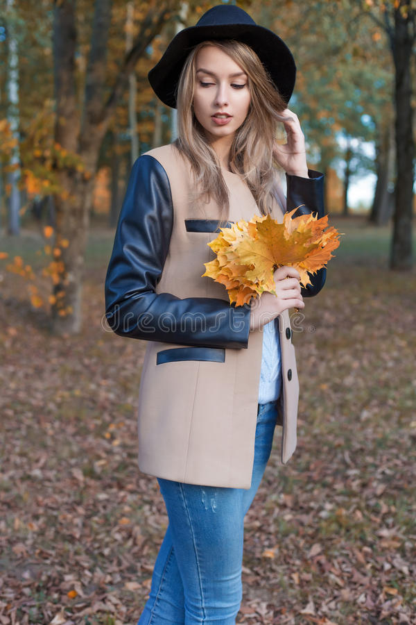 La muchacha alegre linda hermosa en un sombrero negro con un ramo de hojas coloreadas brillantes en una capa camina en parque del imagenes de archivo