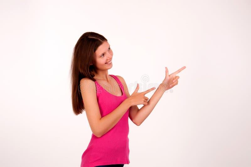 La muchacha alegre muestra la dirección con los fingeres en el lado imágenes de archivo libres de regalías