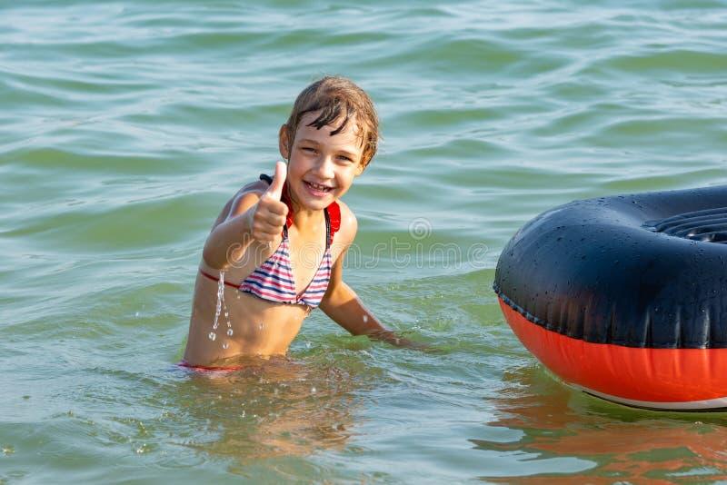 La muchacha alegre muestra el pulgar para arriba saltando de un barco imagen de archivo libre de regalías