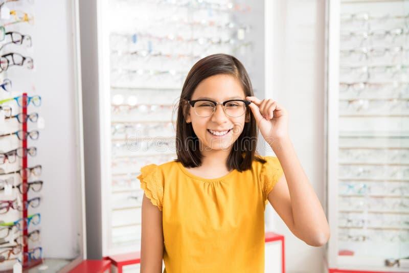 La muchacha alegre que decide comprar nuevas gafas en óptico almacena w fotos de archivo
