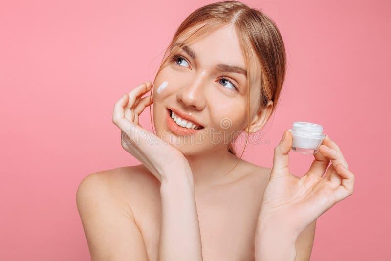 La muchacha alegre sostiene una crema hidratante en su mano y la aplica a su cara para hidratar la piel y para quitar arrugas imagenes de archivo