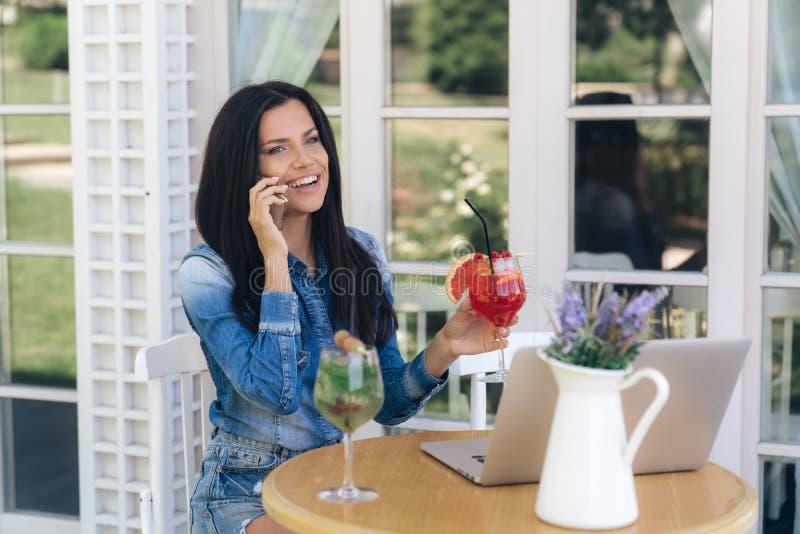 La muchacha alegre tiene un aspecto europeo, se sienta en una tabla en un café, ríe, habla en el teléfono, sonrisas cuidadosament imagen de archivo libre de regalías