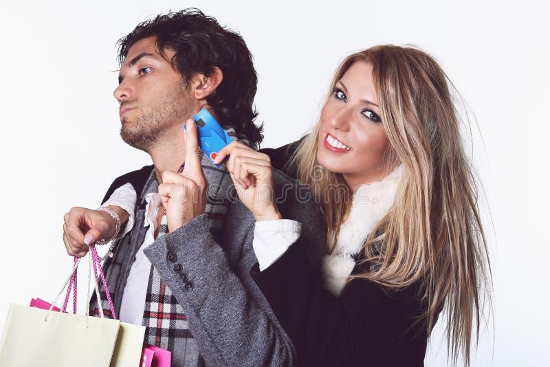 La muchacha alegre toma la tarjeta de crédito del novio imágenes de archivo libres de regalías