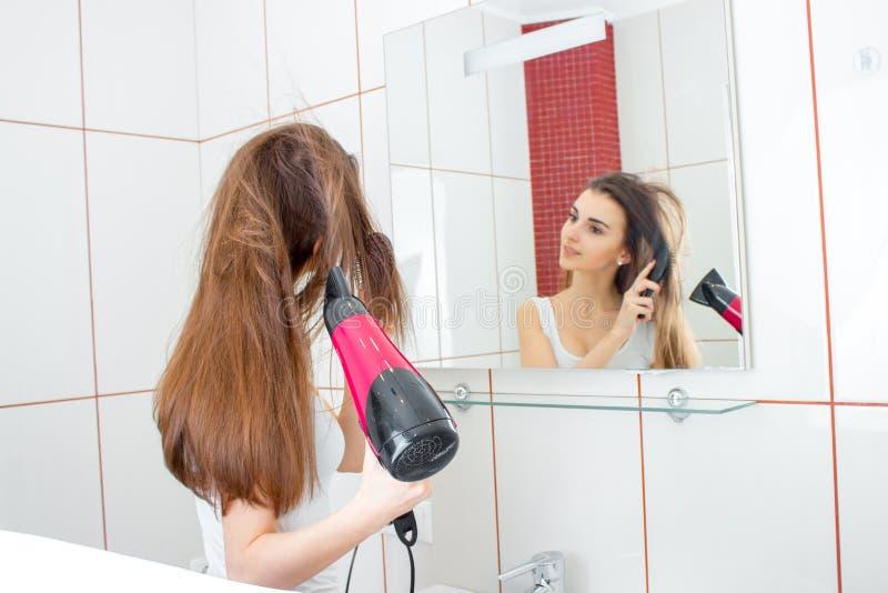 La muchacha antes del espejo el cabello seco imagenes de archivo