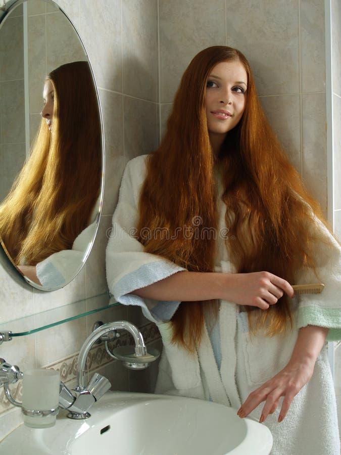 La muchacha aplica el pelo con brocha hermoso largo en un cuarto de baño imagen de archivo libre de regalías