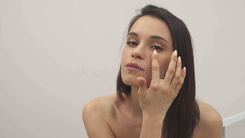 La muchacha aplica el tratamiento facial fotografía de archivo libre de regalías