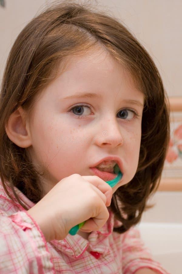 La muchacha aplica los dientes con brocha imagen de archivo libre de regalías