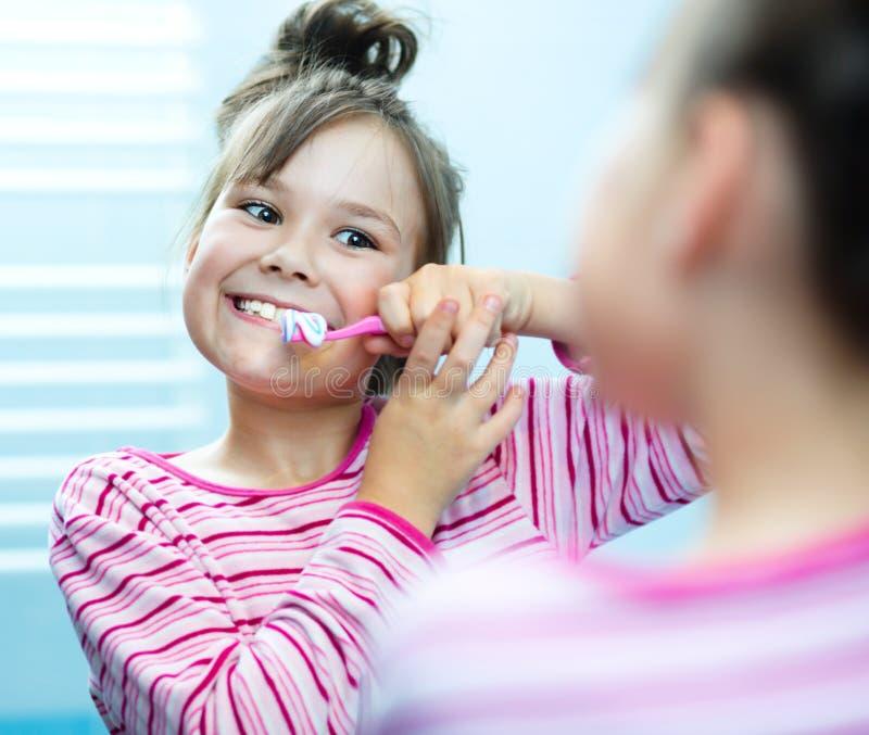 La muchacha aplica sus dientes con brocha fotografía de archivo