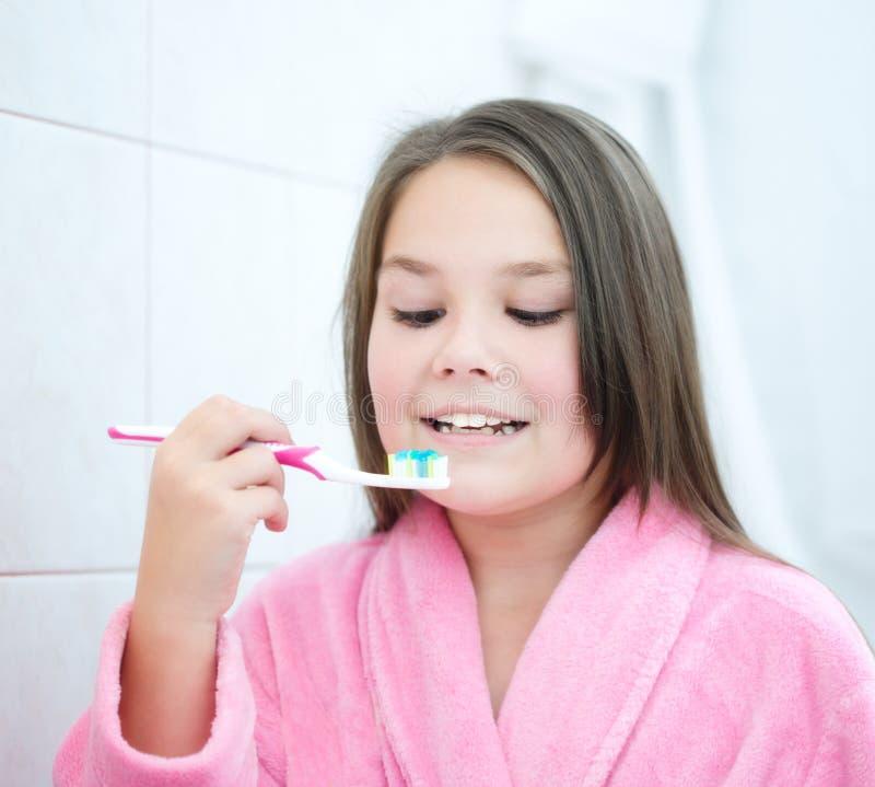 La muchacha aplica sus dientes con brocha foto de archivo libre de regalías