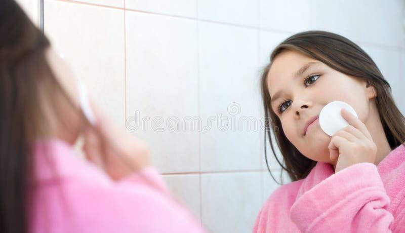 La muchacha aplica sus dientes con brocha foto de archivo