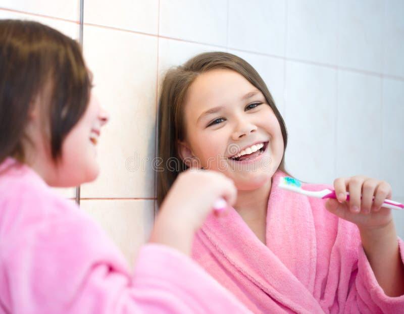 La muchacha aplica sus dientes con brocha imagen de archivo