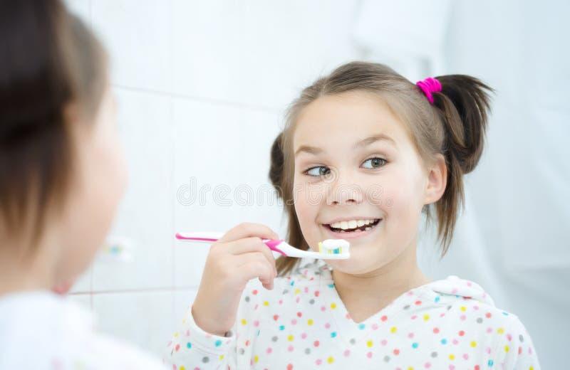 La muchacha aplica sus dientes con brocha fotos de archivo