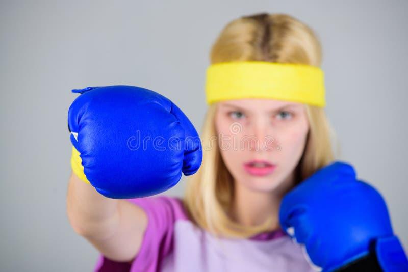 La muchacha aprende cómo defenderse Mujer que ejercita con los guantes de boxeo Concepto del deporte del boxeo Ejercicios de enca fotos de archivo