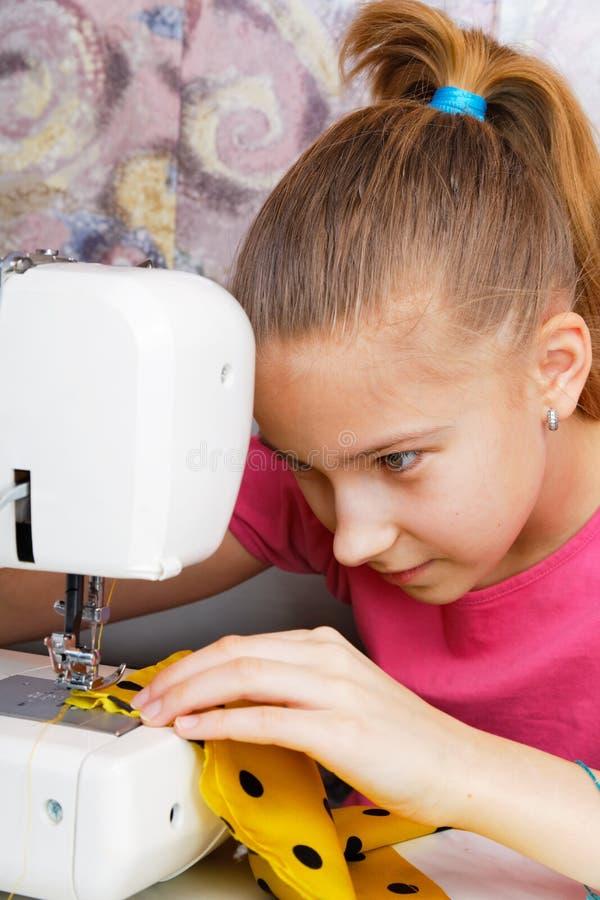 La muchacha aprende coser fotografía de archivo