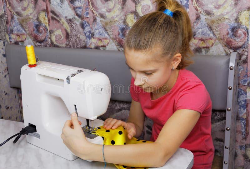 La muchacha aprende coser imagen de archivo