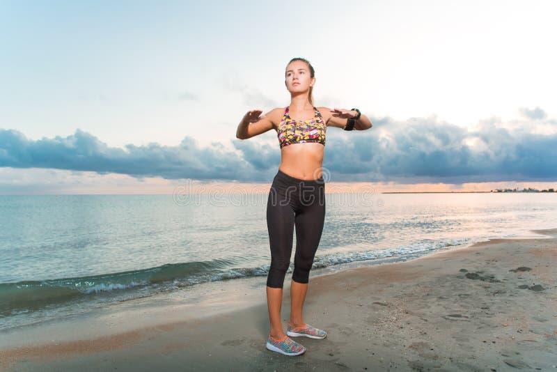 La muchacha apta de los jóvenes que hace mañana ejercita en la playa en la salida del sol fotografía de archivo libre de regalías