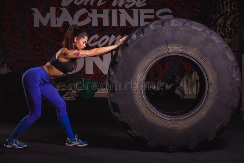 La muchacha apta en deporte viste mover de un tirón el neumático en el gimnasio fotos de archivo