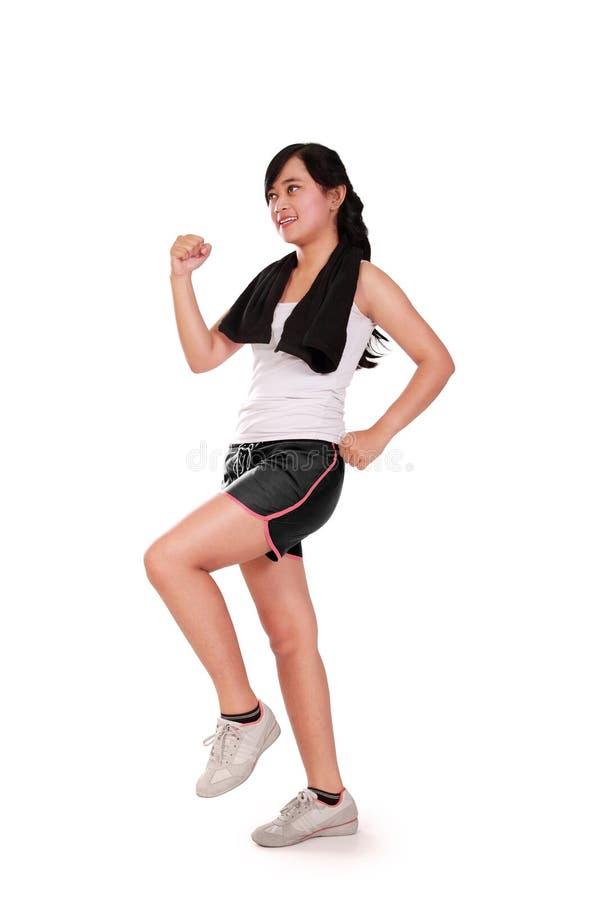 La muchacha apta hace aeróbicos imagen de archivo