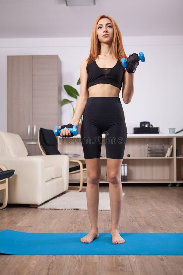 La muchacha apta que hace el bíceps delantero se encrespa durante su entrenamiento de los brazos del hogar imagen de archivo libre de regalías