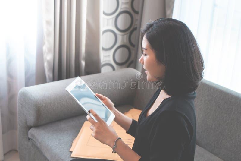 La muchacha asiática addited a las compras en línea, llenas de caja deliveried fotos de archivo