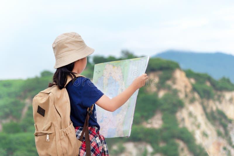 La muchacha asiática de los niños que lleva a cabo mapas y viaje del compás magnético hace excursionismo la situación en la monta imagenes de archivo
