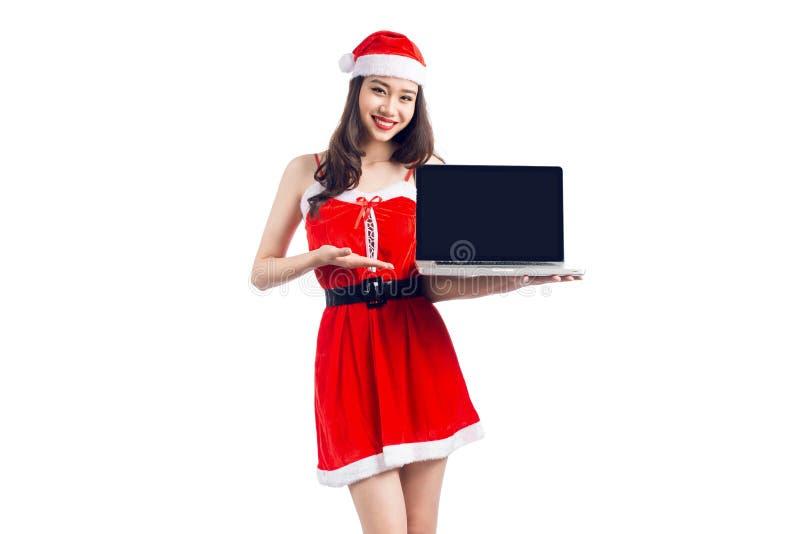 La muchacha asiática de la Navidad con Santa Claus viste llevar a cabo la ISO del ordenador portátil foto de archivo libre de regalías