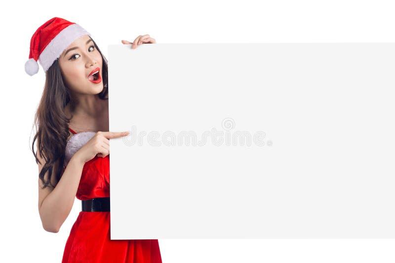 La muchacha asiática de la Navidad con Santa Claus viste llevar a cabo la muestra en blanco fotografía de archivo libre de regalías