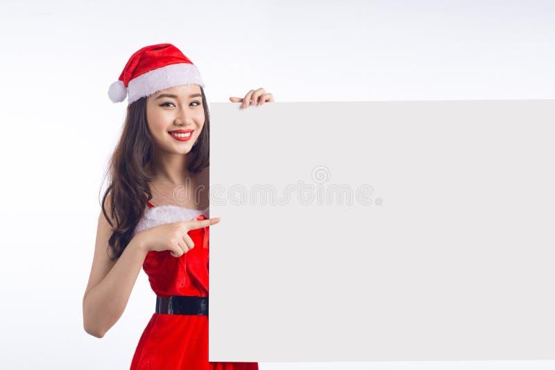 La muchacha asiática de la Navidad con Santa Claus viste llevar a cabo la muestra en blanco fotos de archivo libres de regalías