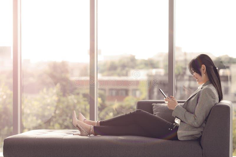 La muchacha asiática de pelo largo se está sentando en el sofá feliz por foto de archivo