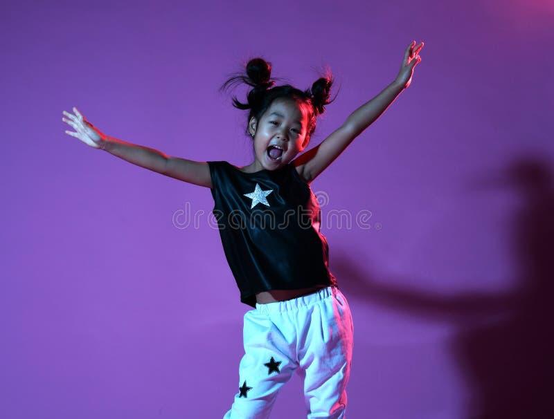 La muchacha asiática del niño de Joyfull en camisa y pantalones con las estrellas en fondo púrpura lanza las manos para arriba co fotografía de archivo