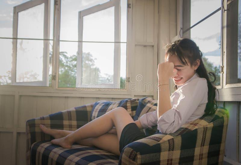 La muchacha asiática es sonriente y de localización en el sofá, mintiendo en el sofá imágenes de archivo libres de regalías