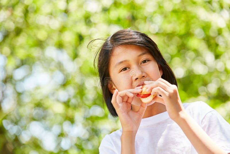 La muchacha asiática está comiendo un baguette fotografía de archivo