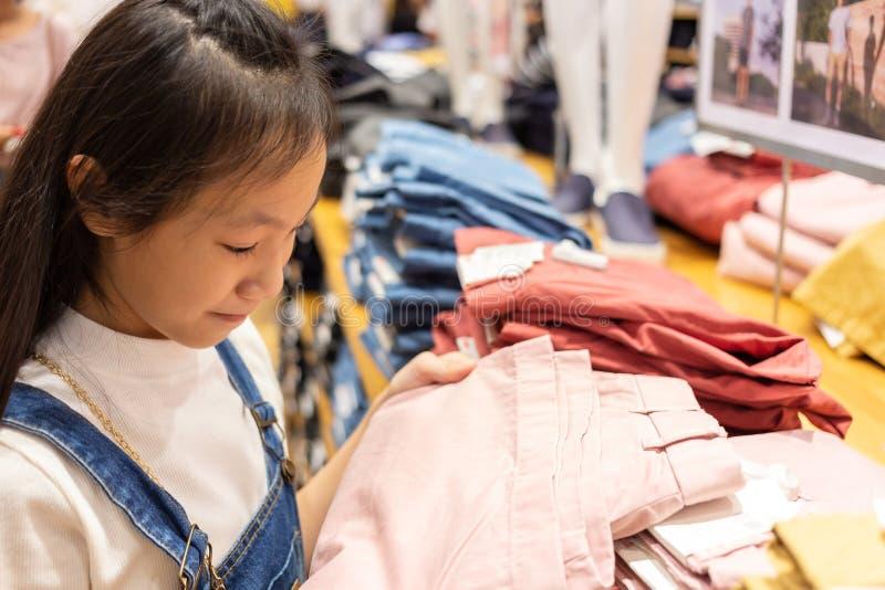 La muchacha asiática feliz está eligiendo la ropa en la tienda de la alameda o de ropa, s imagenes de archivo
