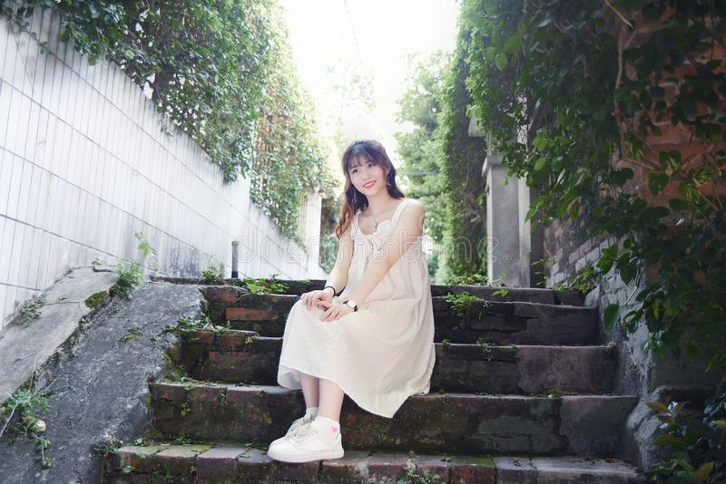 La muchacha asiática hermosa y preciosa muestra su juventud en el parque fotografía de archivo