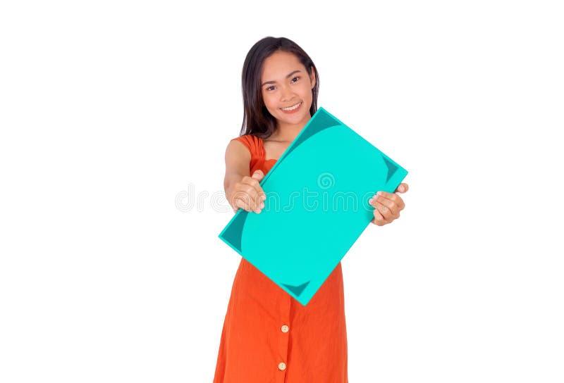 La muchacha asiática joven en vestido anaranjado muestra un Libro verde grande al fondo blanco de la cámara fotos de archivo libres de regalías