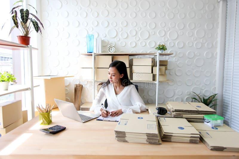 La muchacha asiática joven es comienzo del freelancer encima de la pequeña dirección de la escritura del propietario de negocio e fotografía de archivo libre de regalías