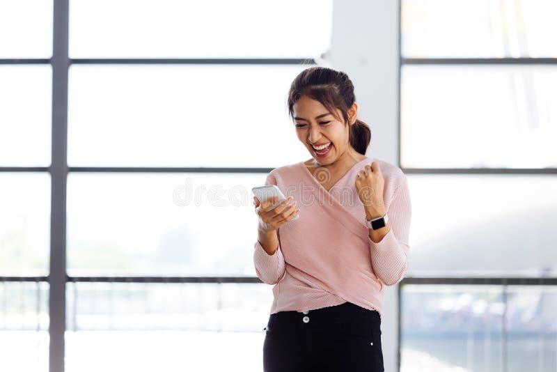 La muchacha asiática joven que mira su teléfono móvil y consigue excitada dentro del edificio fotos de archivo
