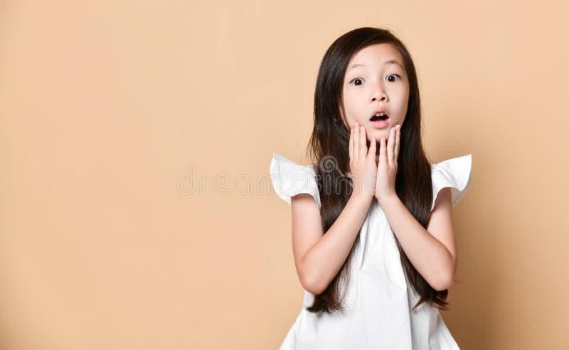 La muchacha asiática joven sorprendió el griterío feliz emocionado Niño alegre con la expresión alegre divertida de la cara foto de archivo