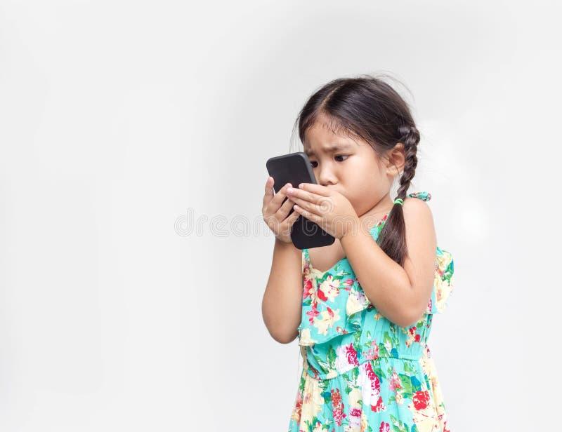 La muchacha asiática mueve el ojo así que el móvil cercano al reloj fotos de archivo libres de regalías