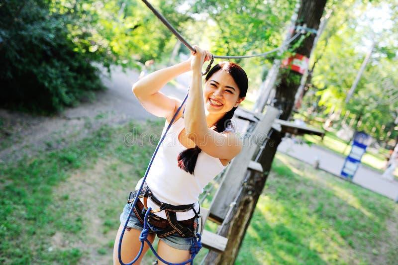 La muchacha asiática pasa curso de las cuerdas de los obstáculos fotografía de archivo