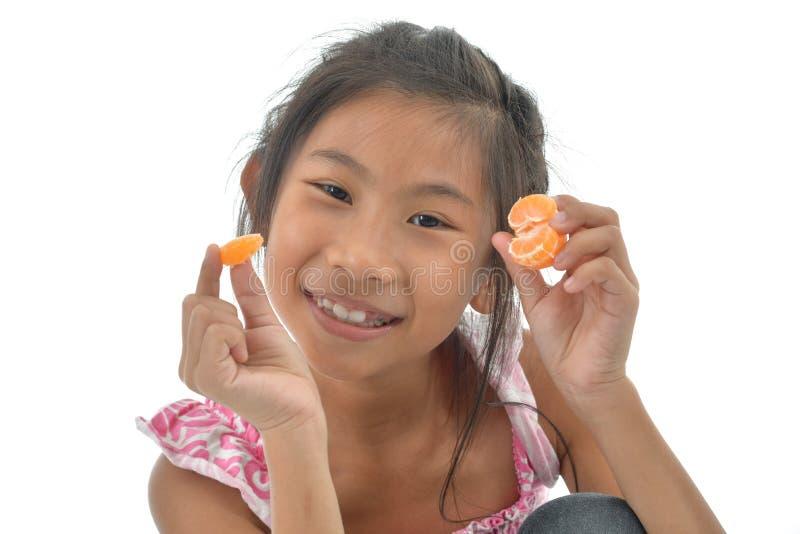 La muchacha asiática que come la naranja y abre su boca en el fondo blanco foto de archivo libre de regalías