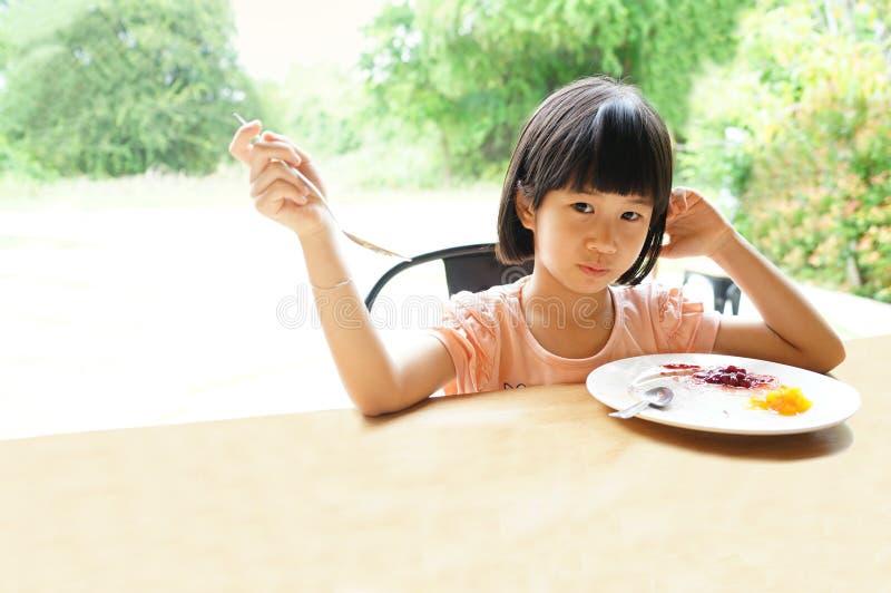 La muchacha asiática 6s come la placa de la comida del desayuno se sienta en tabla imagen de archivo