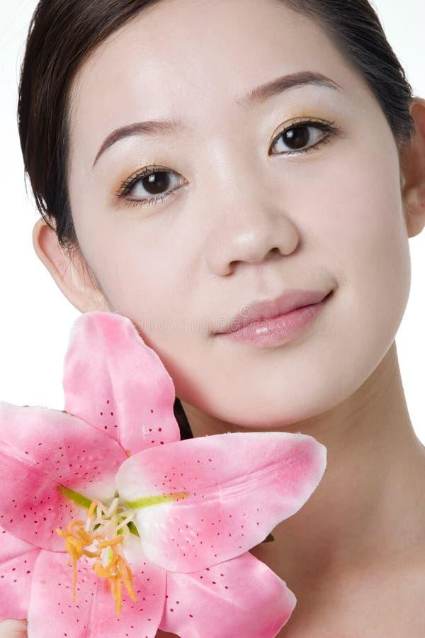 La muchacha asiática sonriente con una mano toca su cara fotos de archivo libres de regalías