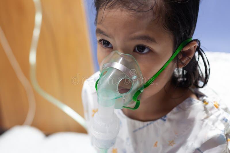 La muchacha asiática tiene asma o el nebulization de la enfermedad y de la necesidad de la pulmonía pasa la máscara del inhalador foto de archivo libre de regalías