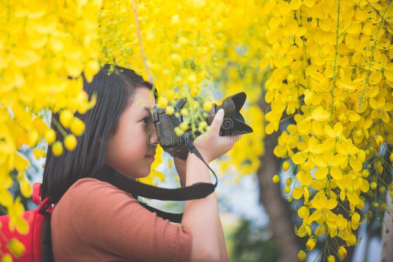 La muchacha asiática toma la foto con la flor amarilla floreciente imágenes de archivo libres de regalías