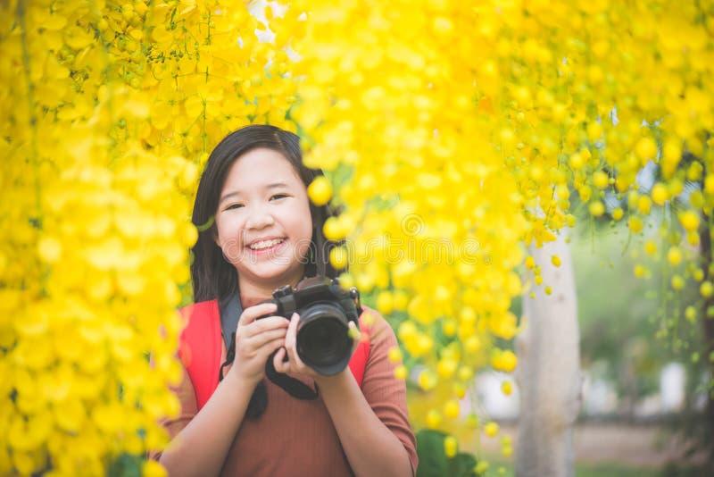 La muchacha asiática toma la foto con la flor amarilla floreciente foto de archivo libre de regalías