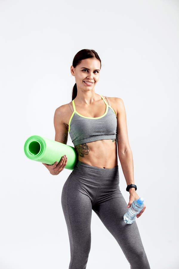 La muchacha atlética bonita vestida en una ropa de deportes gris se coloca con la estera de la aptitud y la botella de agua en su foto de archivo libre de regalías